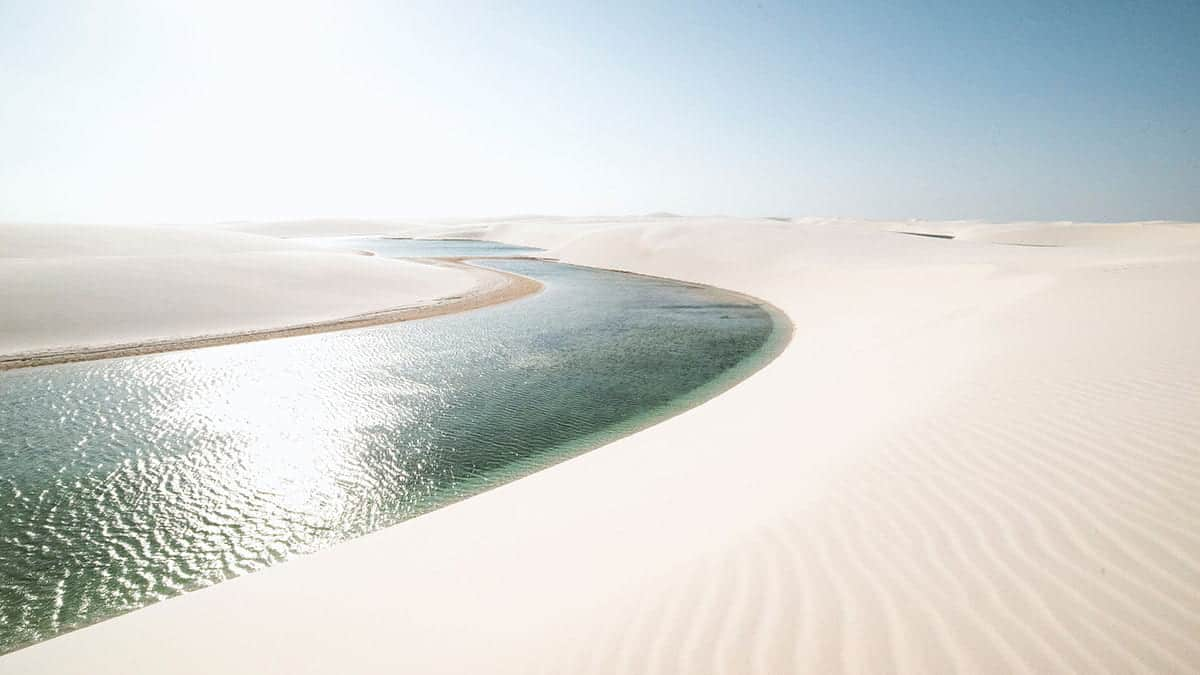 Paisagem de praia em beira de rio, com areia branca e muito sol