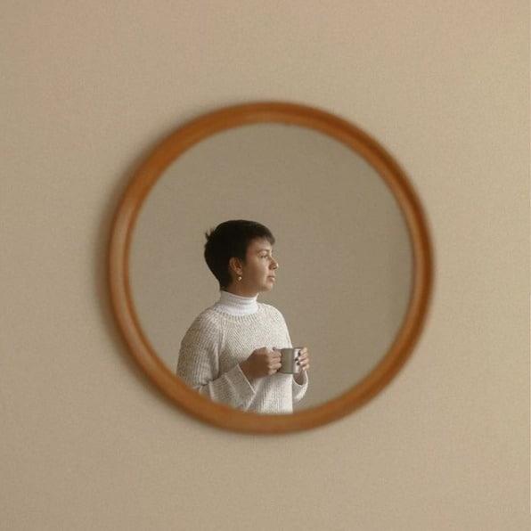 Espelho em parede, refletindo a imagem de Lua Couto segurando uma caneca de chá