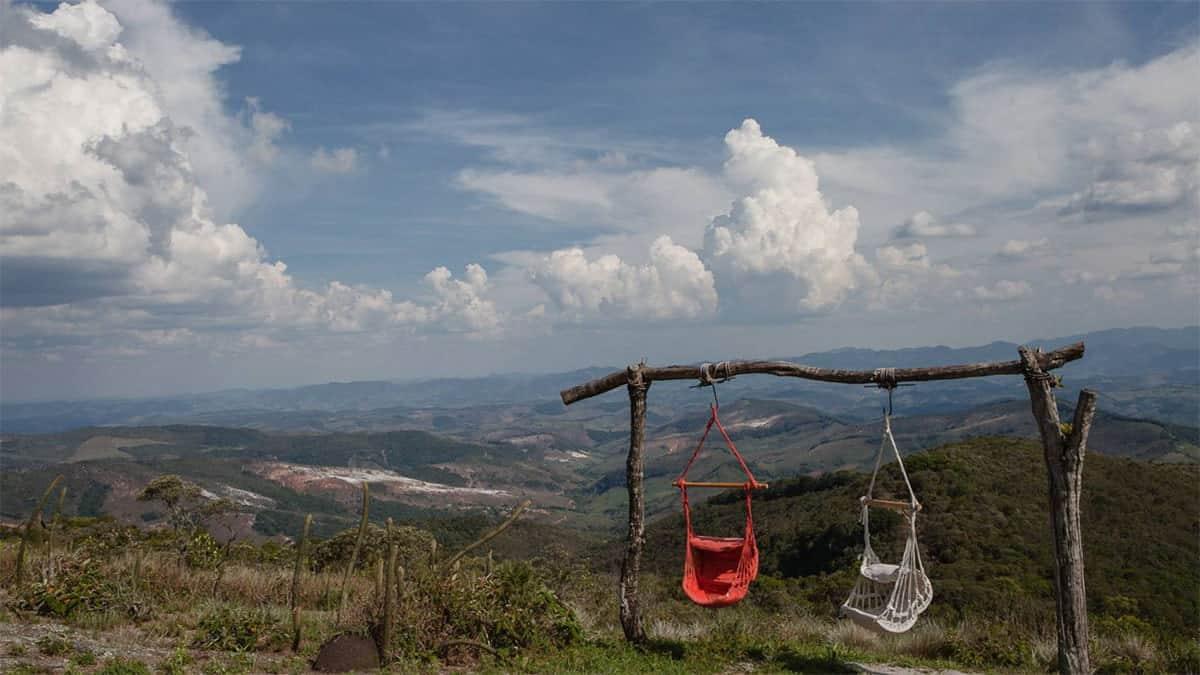 Paisagem de horizonte visto do alto de uma montanha, com estrutura de madeira e dois balanços feitos de crochê