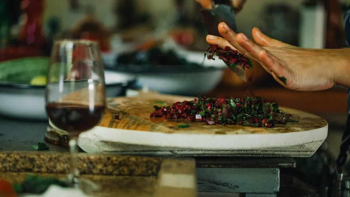 Mãos da chef de cozinha Lis Cereja cortando beterraba e ervas em bancada de cozinha