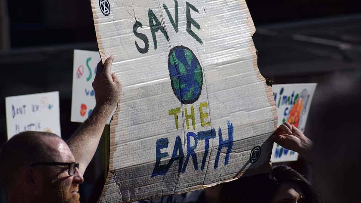 """Homem segura cartaz em manifestação pelo clima, com os dizeres: """"Save the Earth"""""""