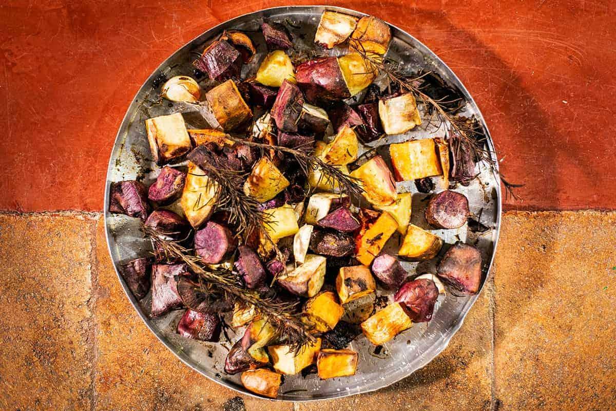Batatas, batatas-doce roxas e laranjas assadas, com ramas de alecrim, sal e azeite