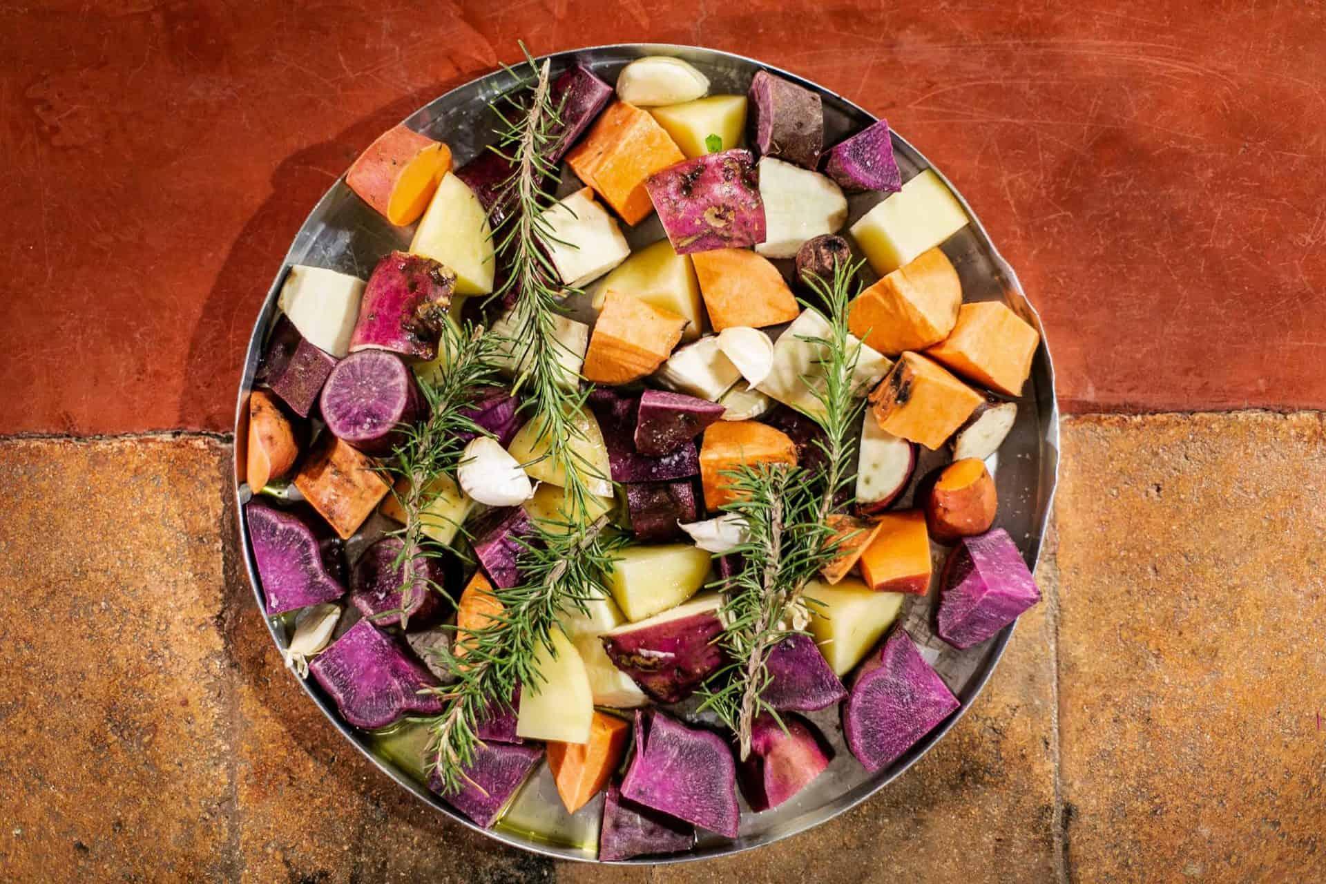Batatas, batatas-doce roxas e laranjas numa assadeira, com uma rama de alecrim, prontas para serem assadas