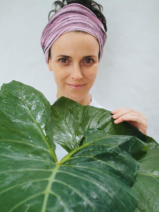 A chef Helena Rizzo posa com folhas de taioba, uma PANC (Planta Alimentícia Não Convencional)