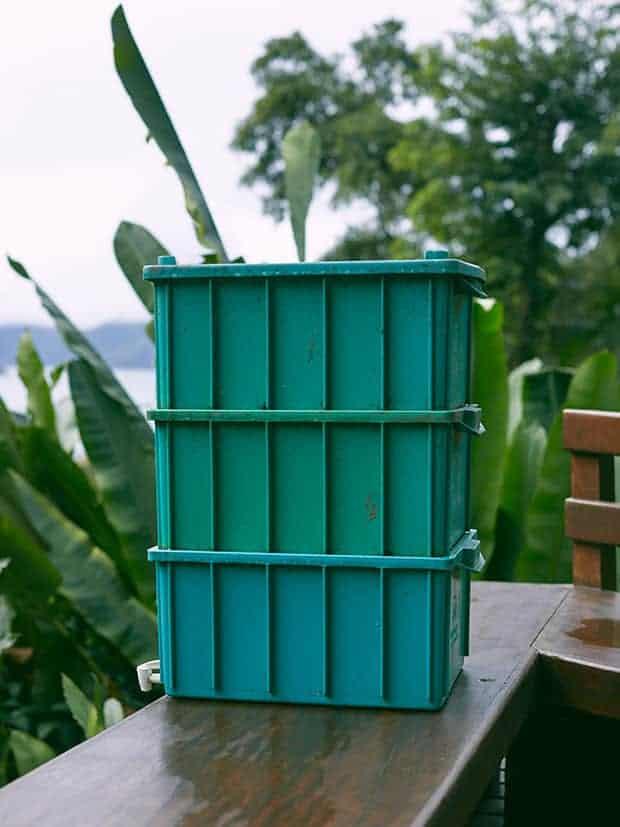 Composteira de plástico verde apoiada em parapeito de madeira. AO fundo, paisagem de serra.