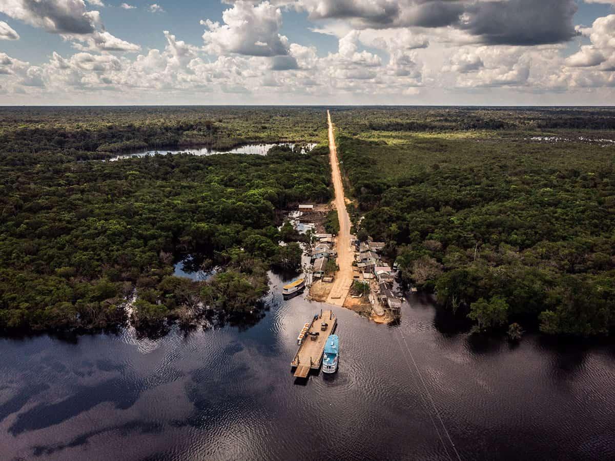 Vista aérea da BR 319, ainda em construção, cortando vilarejo na Amazônia