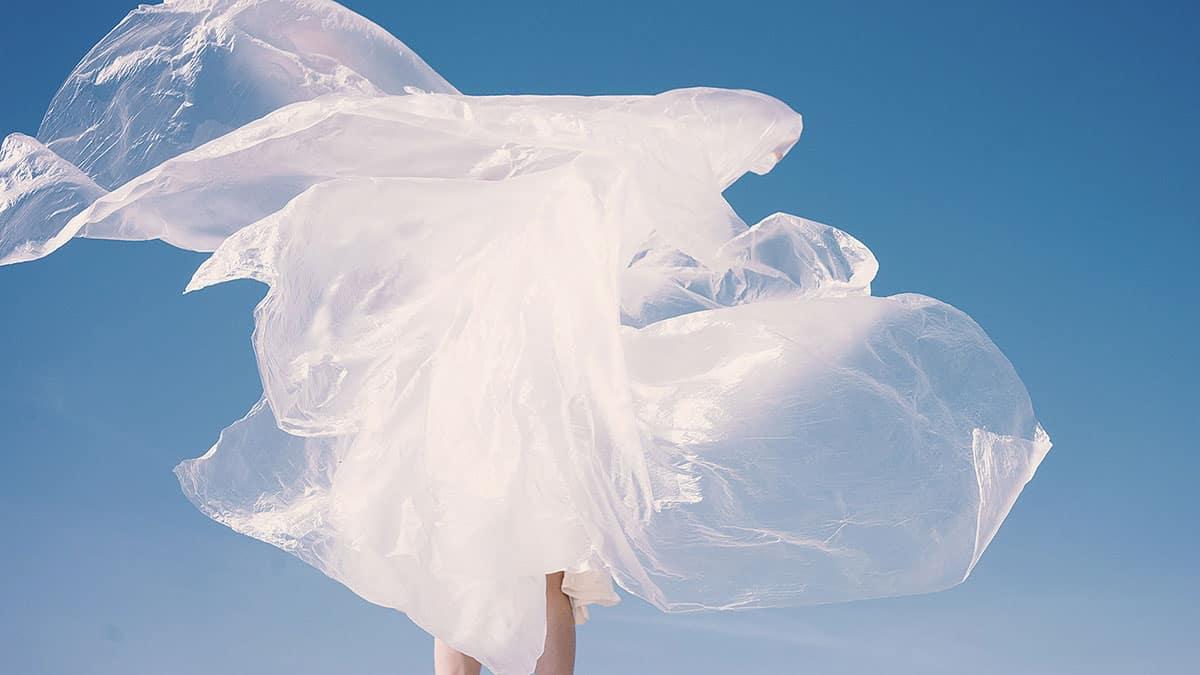 Mulher envolvida em plástico, como um vestido plástico voando com o vento para falar de roupas e poluição