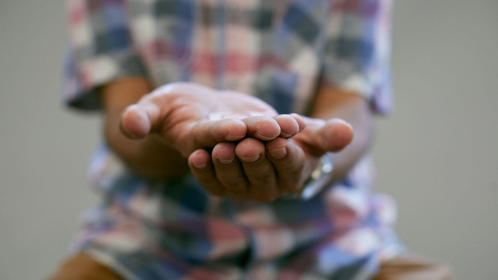 Omar Suleibi, refugiado sírio no Brasil, mostra as mãos em gesto de pedido de auxílio, em ensaio de fotos para o projeto Retrato Social. Foto: Loiro Cunha