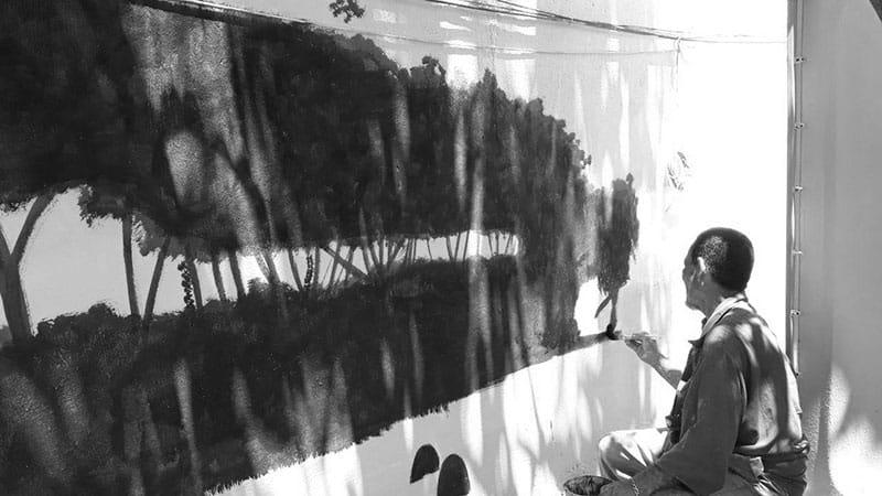 Refugiado pinta um mural, em projeto de arte e educação para refugiados, da FFHI em Roraima
