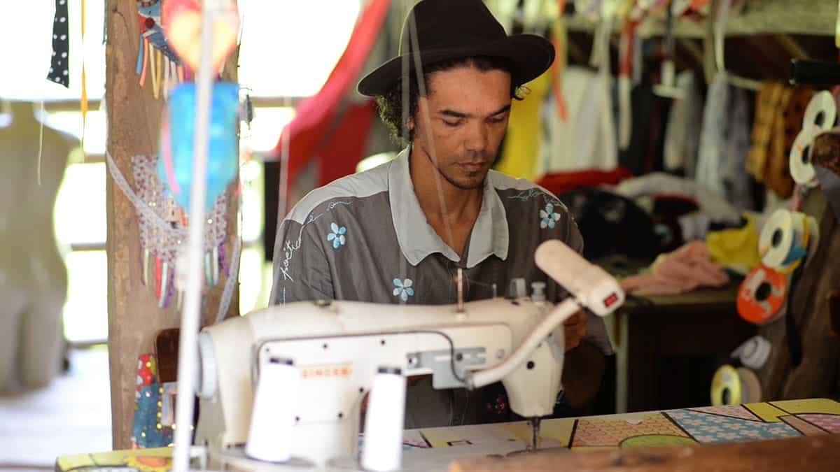 O estilista e poeta Teko Semente costurando em seu atelier