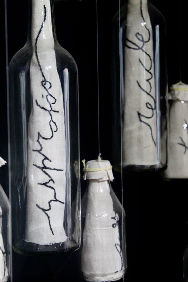 Instalação em exposição do estilista e poeta Teko Semente: tecidos dentro de garrafas penduradas