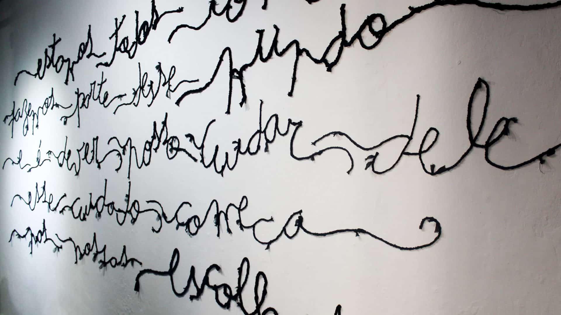 Poesia bordada, aplicada em parede, em exposição do estilista e poeta Teko Semente