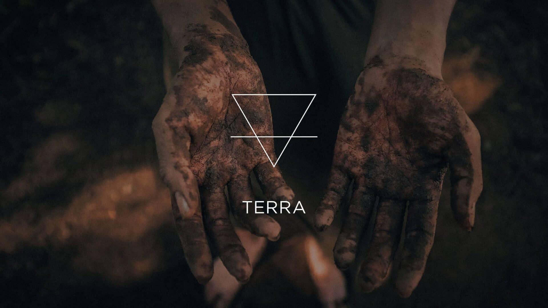 Mãos sujas de terra e o símbolo do elemento Terra