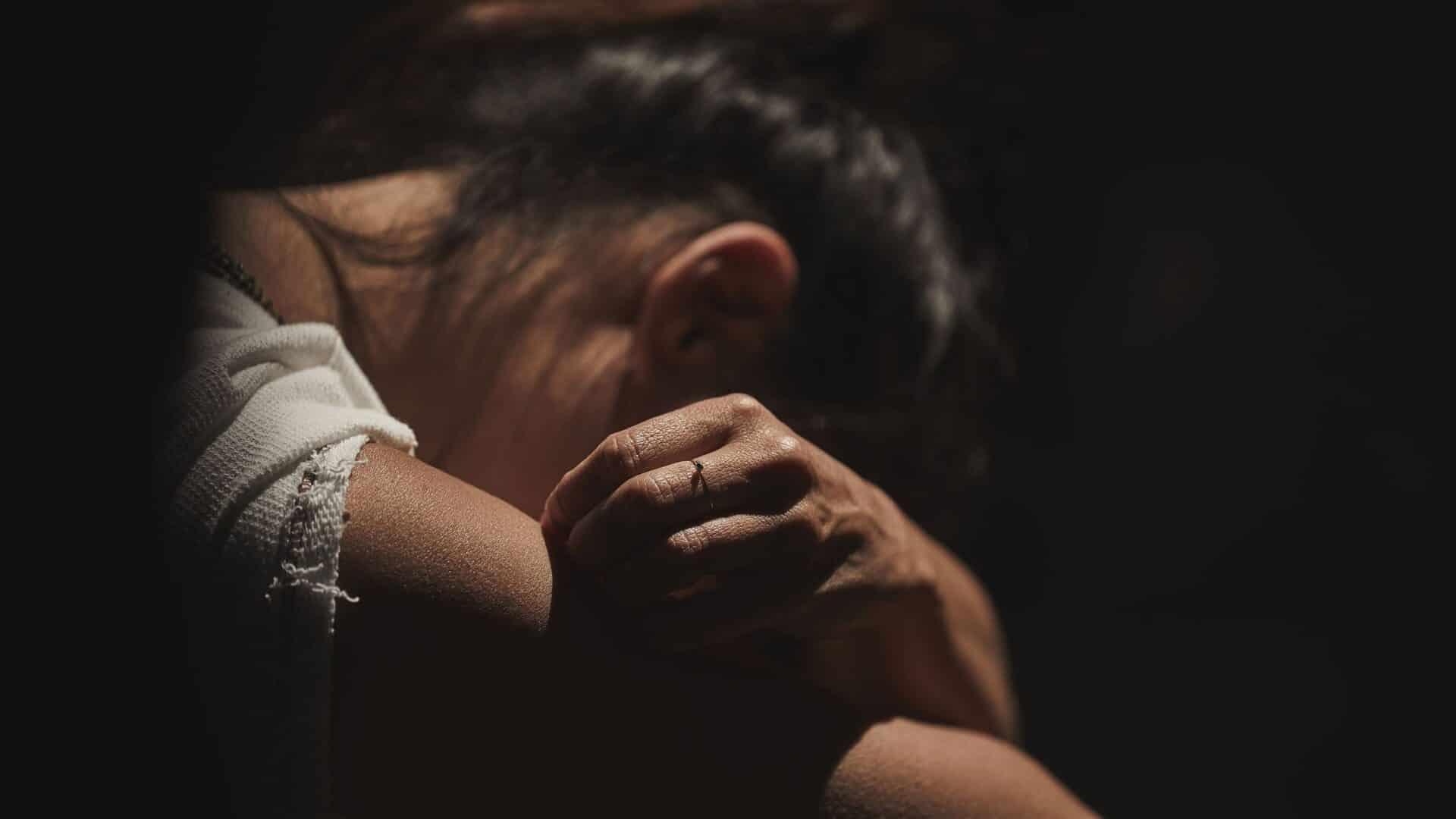 Mulher agachada com o rosto coberto pelos braços